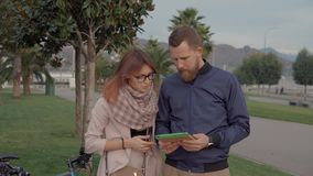 Young man and woman are viewing map of city in tablet screen, standing in park stock video footage