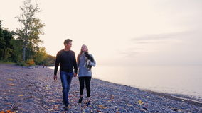 Young man and woman walking along the beach at sunset. A woman carries a puppy in hand stock video footage