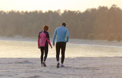 Young man and woman walking along the waterfront Stock Photography
