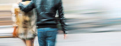 Young man and woman walking down the street Stock Photography