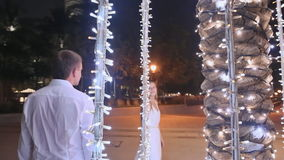 Young man and woman walking among glowing palms trees at night in the city. Girl with love looking at the guy. Dubai. Young man and woman walking among glowing stock footage