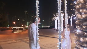 Young man and woman walking among glowing palms trees at night in the city. Girl with love looking at the guy. stock footage