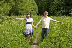 Young man and woman walking on a meadow Royalty Free Stock Image