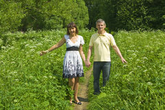Young man and woman walking on meadow in blossom Stock Photography