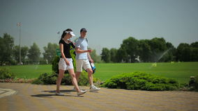 The young man and woman walking near golf field stock video