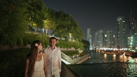 Young man and woman walking in the night Dubai stock footage