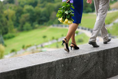 Young man and woman walking on a parapet wall Stock Photo