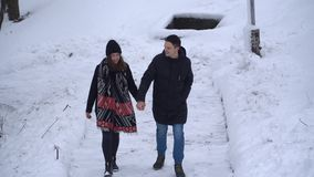 Young man and woman in love walking in winter park covered with snow holding hands. Winter outdoor leisure of happy stock video