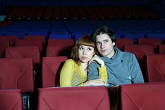 Young man and woman watch movie, embrace Royalty Free Stock Photography