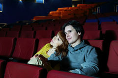 Young man and woman watch movie, embrace and smile Royalty Free Stock Photos