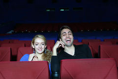 Young man and woman watch movie and laugh in movie theater Stock Images