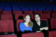 Young man and woman watch movie in movie theater Stock Photos