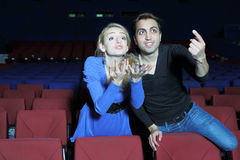 Young man and woman watch movie and root for movie characters Stock Image