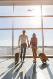Young man and woman watching aircraft flight. Dreamful loving couple is ready for travel. They are standing near window at airport and looking at flying plane Stock Photos