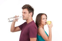 Young man and woman with water and apple. Addicted men standing on white background Royalty Free Stock Photography