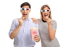 Young man and woman wearing 3D glasses and eating popcorn Royalty Free Stock Photo