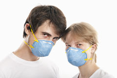Young man and woman wearing  respirators. Couple  in blue face masks  with heads together  against white background Stock Images
