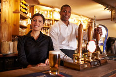 A young man and woman working behind a bar look to camera stock image