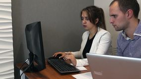 Young man and woman are working on a computer.  stock footage
