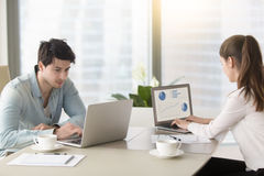 Young man and woman working at office table using laptops royalty free stock image