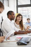 Young man and woman working in an open plan office, vertical Royalty Free Stock Images