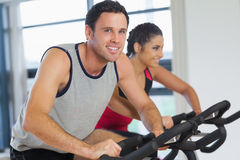 Young man and woman working out at spinning class Stock Photos