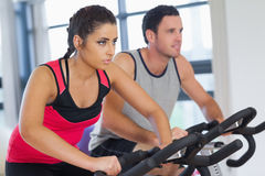 Young man and woman working out at spinning class Stock Photography