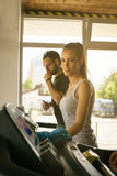 Young man and woman workout in gym. Stock Images