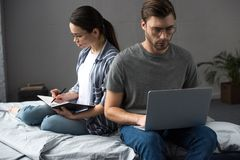 Young man and woman writing in notepad and working on laptop while sitting stock images