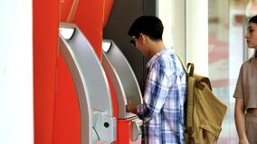 Young man and women come cash from the ATM