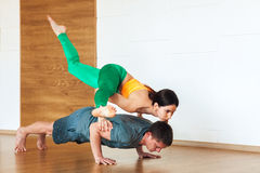 Young man and women in difficult forward bending yoga posture. Family Yoga Stock Photos