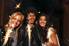 Young man and women enjoying new years eve. Young men and women enjoying new years eve outdoors stock image