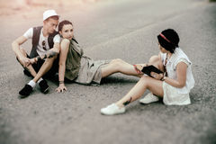 Young man and women hipsters have a rest on road Royalty Free Stock Photos