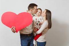 Beautiful European young people on a white background. Emotions, family concept. Young man, women holding, kissing, hugging little cute child boy with big red stock photography