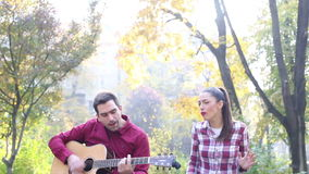 Young man and women playing guitar and singing in park stock footage