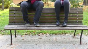 Young man and women playing guitar and singing in park. Handsome young man and beautiful women playing guitar and singing while sitting on bench in park stock footage
