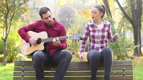Young man and women playing guitar and singing in park stock video footage