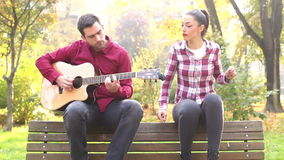 Young man and women playing guitar and singing in park. Handsome young man and beautiful women playing guitar and singing while sitting on bench in park, graded stock footage