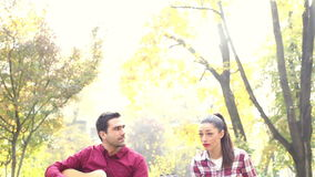 Young man and women playing guitar and singing in park. Handsome young man and beautiful women playing guitar and singing while sitting on bench in park, graded stock video