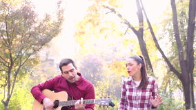 Young man and women playing guitar and singing in park stock video