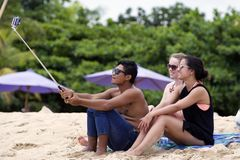 Young man and women wearing sunglasses takes selfi with using a selfie stick on the beach. Young man and women wearing sunglasses, swimsuits  and a blue jeans Royalty Free Stock Images