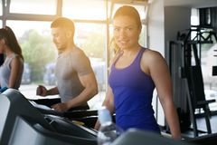 Young man and women workout in gym. stock photography