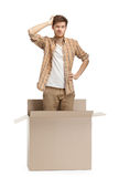 Young man wonders. Why he is inside the box, isolated, white background Royalty Free Stock Images
