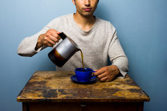 Young man at wooden table pouring coffee Stock Photos