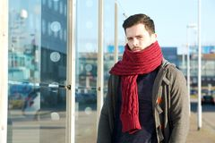 Young man with wool scarf and winter jacket. Close up portrait of a young man with wool scarf and winter jacket standing outside royalty free stock photos