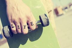 Young man with the word life tattooed in his hand with a skatebo Royalty Free Stock Image