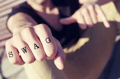 Young man with the word swag tattooed in his fist, with a filter. Closeup of a young man showing his fist with the word swag tattooed in his knuckles, with a Royalty Free Stock Photo