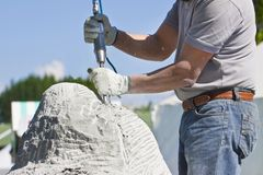 Young man at work with compressed air chisel and protective gloves to carving a stone block.  royalty free stock photography