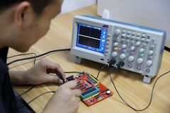 Electronic devices and Circuit board ,male electronic engineer using oscilloscope in laboratory royalty free stock image