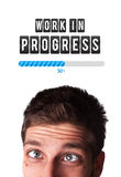 Young man with Work in progress mark over his head Royalty Free Stock Image